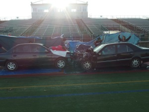 A photo of the scene yesterday during Mock Crash. People hold up the tarps to cover the cars until the time to reveal.